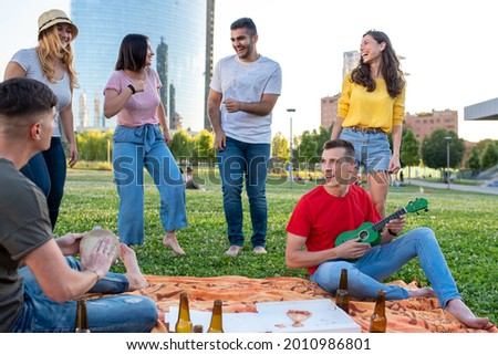 young boys playing ukulele and tambourine, people dancing barefoot on the lawn, scene of a pic nick with city skyline, millennials having a party with beers and pizza, couple having fun in a park