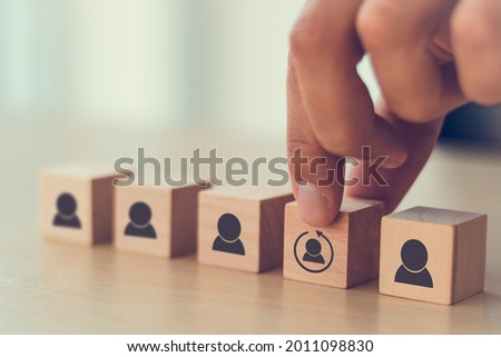 Re-skill concept to training employees on an entirely new set of skills for business growth and digital transformation. Man holds wood cube with re-skill icon on many staff icon symbol;  Copy space.  Royalty-Free Stock Photo #2011098830
