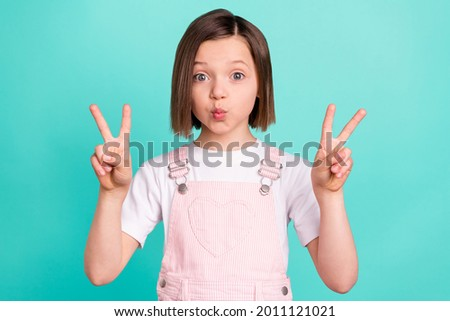 Photo of funny happy cheerful young girl send air kiss make v-signs isolated on pastel teal color background