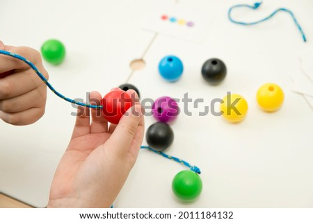 Primary Lacing Beads - Educational Toy With Wooden Balls. Colourful rainbow wooden lacing toy for toddlers. Threading toy for fine motor skills development. Boy holding ball with lace Royalty-Free Stock Photo #2011184132