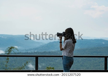 A woman in white t-shirt and jean using dslr camera to taking mountain view at view point near metal fence. Traveler taking mountain photo.