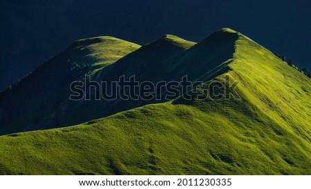Gartner Berg at sunrise, with early morning light on grass fields on top of the mountain