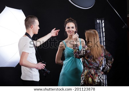 Make-up artist working during photo session, horizontal