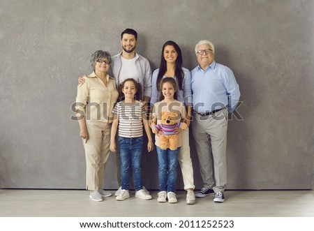 Studio photoshoot group portrait of happy big extended multi generational family. Cheerful mom, dad, grandma, grandpa and two little daughters with toy standing together, looking at camera and smiling Royalty-Free Stock Photo #2011252523