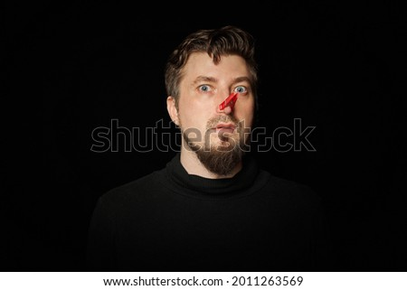 Bearded man with clothespin on nose. Bad stink, funny prankster, joke concept. Laugh at yourself. Red clothespin - symbol of self-mockery and joking character. Black background.