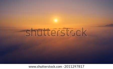 Foggy weather at sunrise. Landscape shot above the fog. Colorful sky with beautiful orange colors. Fantasy picture. Aerial view.
