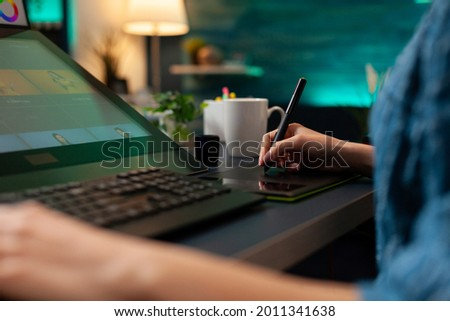 Close up of artistic hand using digital tablet and stylus while retouching image design at professional studio office desk. Woman doing editing work on editor software with modern equipment