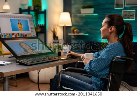 Photo editing software expert retouching work at desk while using professional digital tablet stylus interface on computer monitor. Woman with editor occupation working on image photo