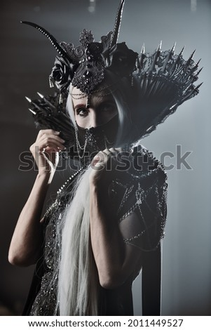 A portrait of fabulous old woman with long gray hair, in a rich headdress and a rich black dress on a gray background. Black Queen, Witch. Halloween. Royalty-Free Stock Photo #2011449527
