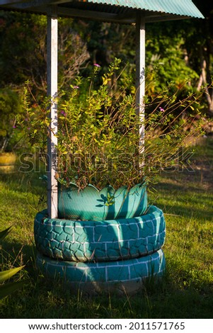 simple design of flower pots from used rubber car tires in city parks. recycle concept from used rubber car  Royalty-Free Stock Photo #2011571765
