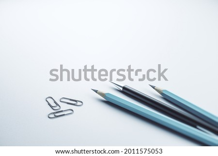 Close up of pencils and paper clips on white mock up layout workplace background, Stationery concept. 3D Rendering