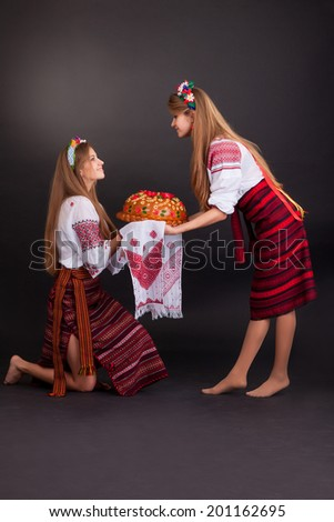Young women in ukrainian clothes, with garland and round loaf on black background #201162695