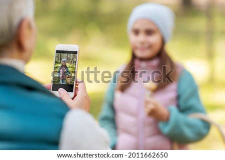 picking season, leisure and people concept - happy smiling grandmother with smartphone photographing granddaughter with mushrooms in basket in forest