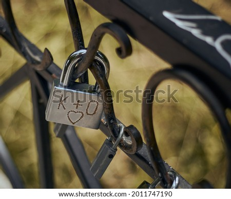 Heart rusty old pad lock on a metal black fence. Symbolism padlock for lovers. Pad lock hangs on the fence. K+O.