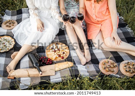 Cropped top picture of three girls, sitting on a blanket on nature, having picnic in a city park during summer holidays or weekends. Women in summer dress, sitting with a glasses of wine at a picnic.
