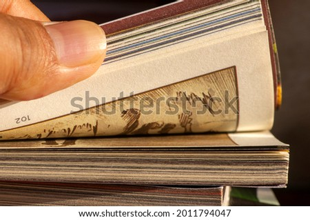 A thumb flipping pages of a comic book in shallow focus Royalty-Free Stock Photo #2011794047