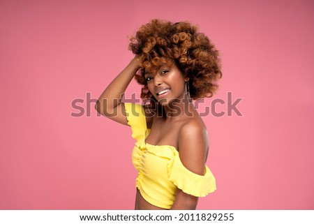Beauty female colorful portrait of happy smiling attractive afro woman with curly hairstyle and glamour summer makeup. Pink pastel studio background. A lot of copy space. Royalty-Free Stock Photo #2011829255