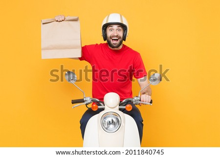 Delivery man helmet red t-shirt uniform driving moped motorbike scooter hold craft paper packet with food isolated on yellow background studio Guy employee working courier Service quarantine concept. Royalty-Free Stock Photo #2011840745