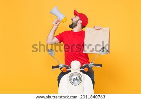 Delivery man in red cap t-shirt uniform driving moped motorbike scooter hold craft paper packet with food isolated on yellow background studio Guy employee working courier Service quarantine concept. Royalty-Free Stock Photo #2011840763