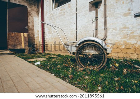 Wheelbarrow on a grass field with an interesting background of an old house . High quality photo Royalty-Free Stock Photo #2011895561