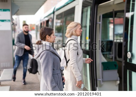 People boarding modern streetcar at public stop in autumn day. Concept of daily city commuting Royalty-Free Stock Photo #2012019401