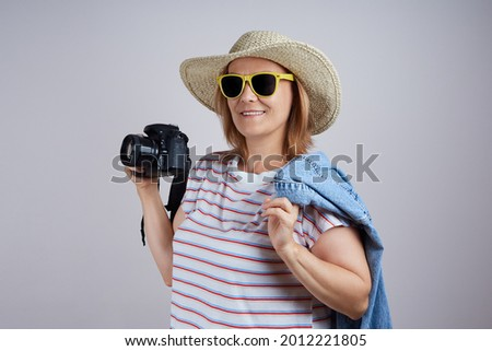 woman tourist in a hat uses a camera, takes a picture. Isolate on gray background.
