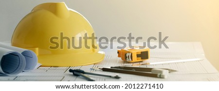 Yellow hard safety helmet hat and the blueprint, pen, ruler, protractor, and tape measure on the table at the construction site.for safety project of workman as engineer or worker,banner copy space.