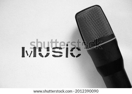 black microphone and the word music in block letters on a white background, music microphone, music, black and white photo, music theme