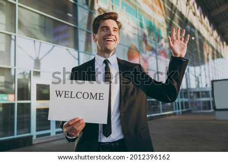 Bottom view young cheerful traveler businessman man in black suit stand outside at international airport terminal hold card sign with welcome title text waving hand Air flight business trip concept.