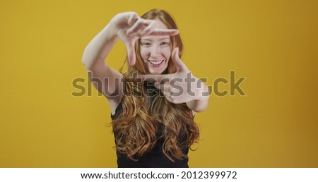 Redhead caucasian woman over yellow isolated background smiling making frame with hands and fingers with happy face. Creativity and photography concept. Film-maker or photographer. Lens vision idea.