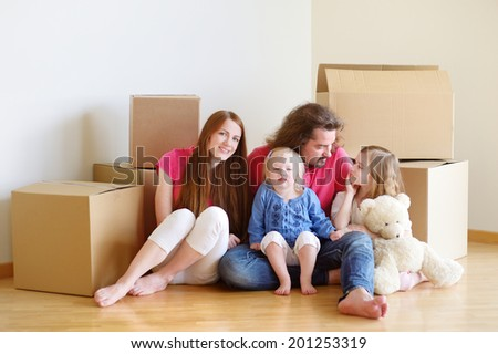 Happy young family sitting on a floor in their new home #201253319