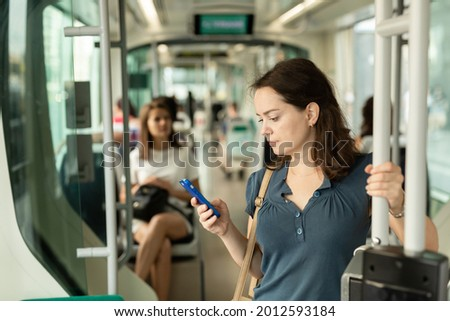 Young woman browsing and typing messages on phone on way to work in modern streetcar .. Royalty-Free Stock Photo #2012593184