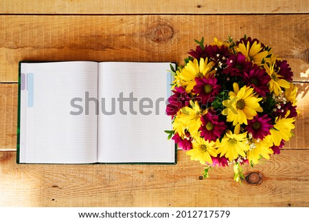 Composition of flowers in a tea mug and a notebook on a wooden table in the morning in summer or spring. Postcard good morning, Happy Mother's Day, March 8th.