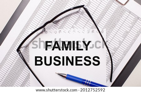 On a light background, a report, black-framed glasses, a pen and a sheet of paper with the text FAMILY BUSINESS. Business concept