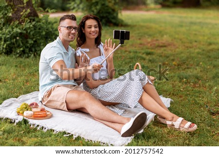 leisure and people concept - happy couple having picnic and taking picture with smartphone on selfie stick at summer park