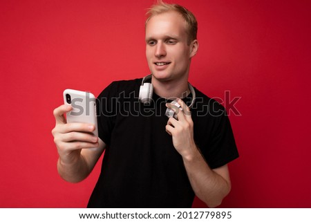 Photo of handsome good looking blonde young man wearing black t-shirt and white headphones standing isolated on red background with copy space holding smartphone and surfing internet on mobile phone