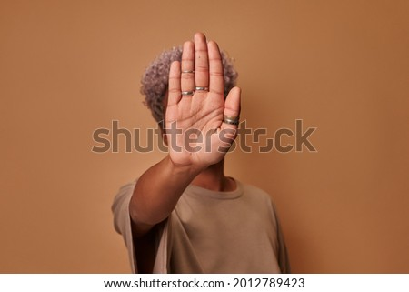 Serious African American woman covers herself with her palm, confidently shows prohibitory gesture stop and no signs shakes her head. Young ethnic woman against violence defends personal boundaries. Royalty-Free Stock Photo #2012789423