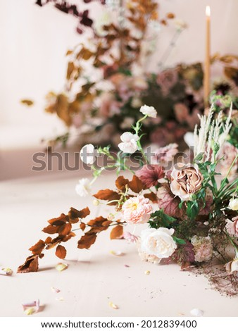 rich floral arrangement with fall leaves and neutral flowers Royalty-Free Stock Photo #2012839400