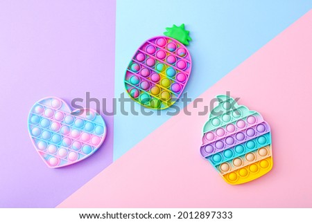 Colorful Push Pop It Bubble Sensory Fidget Toys of different shapes on colorful background, top view Royalty-Free Stock Photo #2012897333
