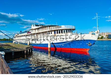 Romantic river cruises. Cruise ship at the pier on the Sheksna river, cityscape Cherepovets Russia.