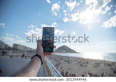 Detail of a man taking a photo with his mobile phone at San Sebastián beach on a sunny day with a clear blue Sky