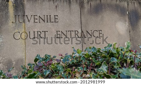 Weathered stone slabs with the words juvenile Court Entrance engraved into it. Royalty-Free Stock Photo #2012981999