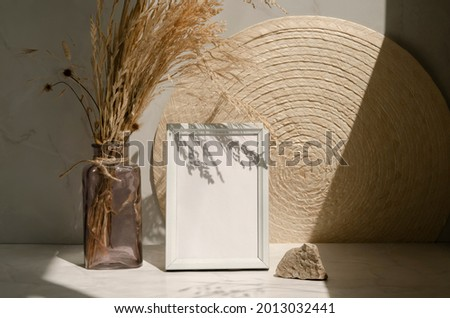 White blank wooden frame mockup. Bouquet of dry herbs in the botlle, napkin and stone. Empty picture frame. Interior design concept. Indoor modern still life with shadows and sunlight.