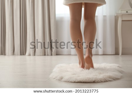 Woman standing on faux fur rug at home, closeup. Space for text Royalty-Free Stock Photo #2013223775