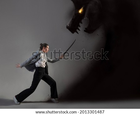 Modern warrior, struggle with external conflicts or internal self-doubt, concept photo art. A young woman in a suit and with a saber fights with a shadow in the form of a beast Royalty-Free Stock Photo #2013301487