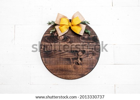 Blank round brown wood sign on white background with fall bow, thanksgiving door decor mockup