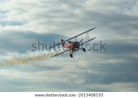 The historic red plane flies against the background of clumping clouds. Royalty-Free Stock Photo #2013408533