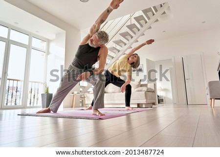 Fit middle aged 50s family couple doing fitness yoga morning exercise at home. Sporty healthy old mature man and woman training together standing in living room. Active seniors sport stretching. Royalty-Free Stock Photo #2013487724
