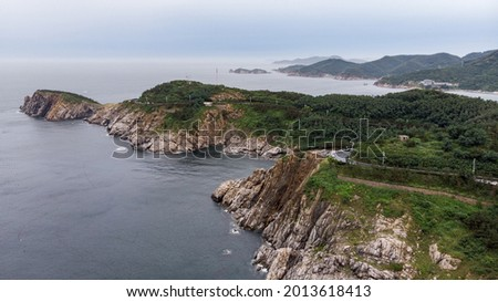 Aerial view of the rugged coastline along the Mao'tou Mountain in Wei'hai, Shan'dong Province, China. The photo was shot on a cloudy day in July.  Royalty-Free Stock Photo #2013618413