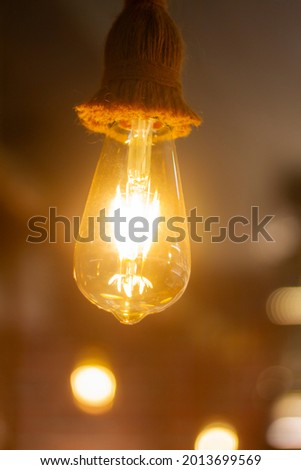 Vintage Light bulb, Lamp hanging with Blurred background at Coffee shop in india for decorate and background picture. selective focus.